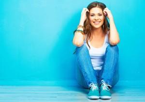 Hipster girl sitting on floor against blue background.